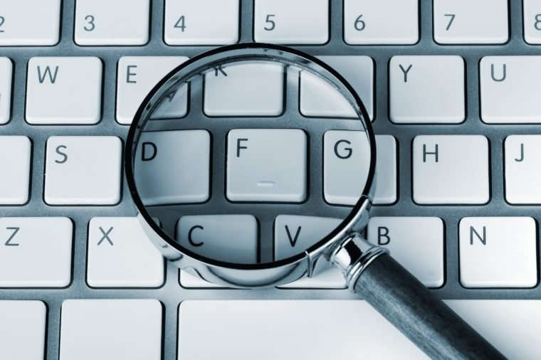 Closeup Magnifying glass on an white keyboard in blue key