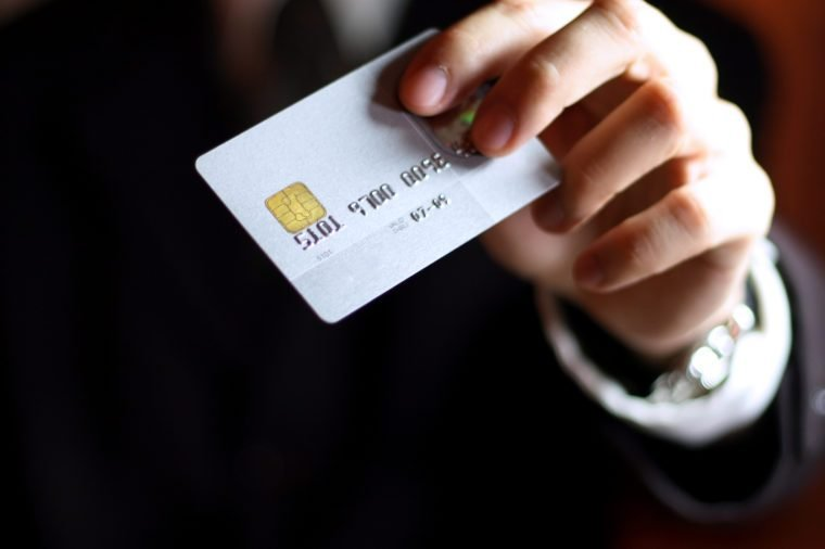 Business man presenting his credit card. Shallow DOF, focus on chip o card. Concept: Shopping and spending.