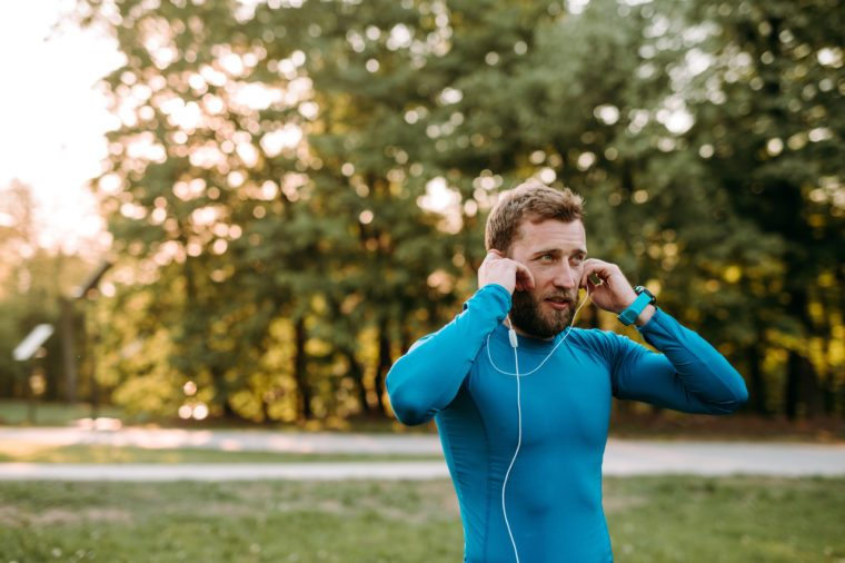Music is always with me. Portrait of athletic mature man before run.