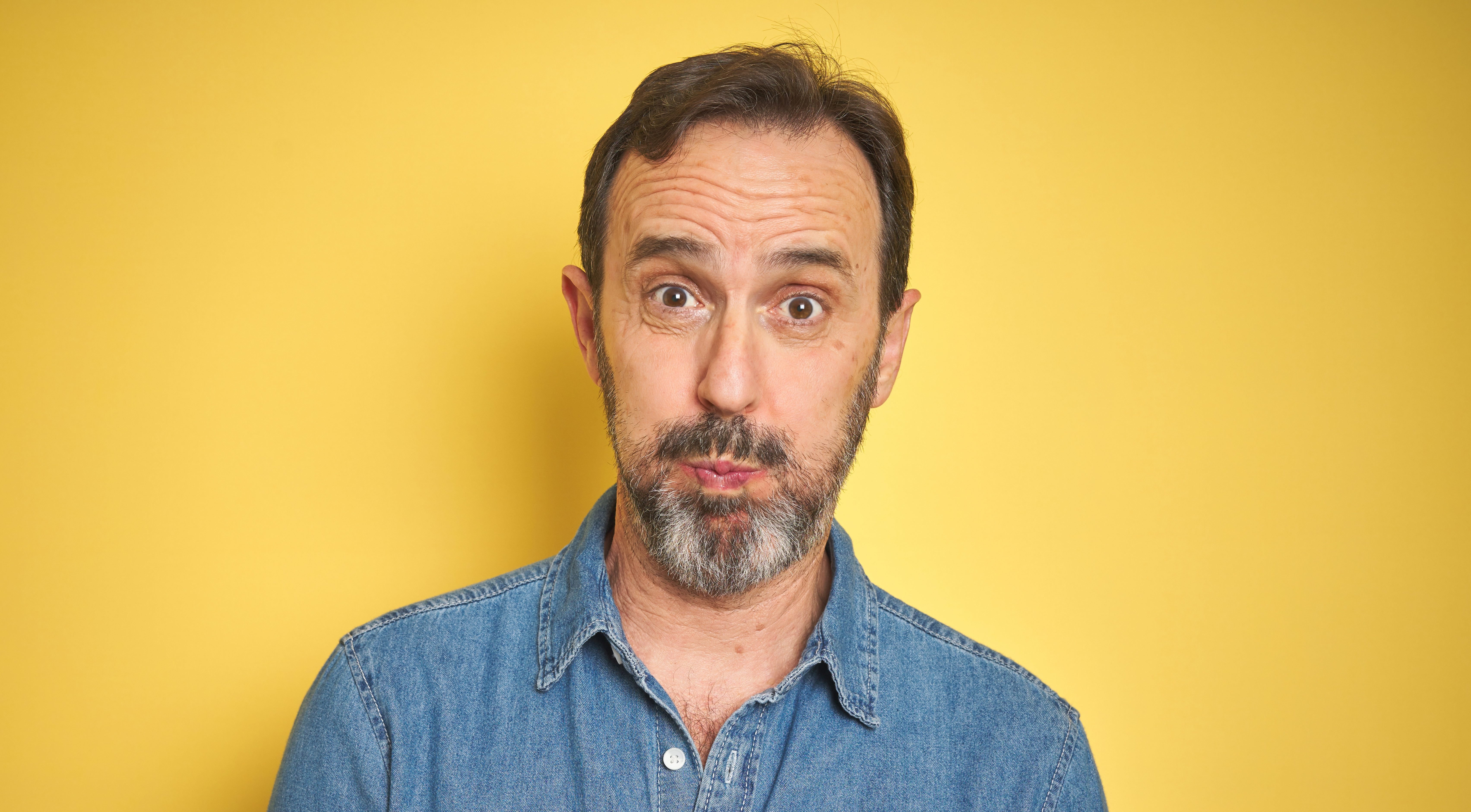 Handsome middle age senior man with grey hair over isolated yellow background puffing cheeks with funny face. Mouth inflated with air, crazy expression.