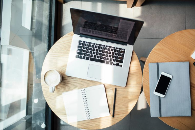 From above photo of laptop and notebook on coffee shop table.