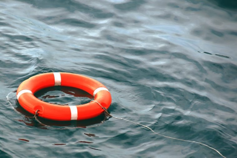 orange life buoy on the waves as a symbol of help and hope