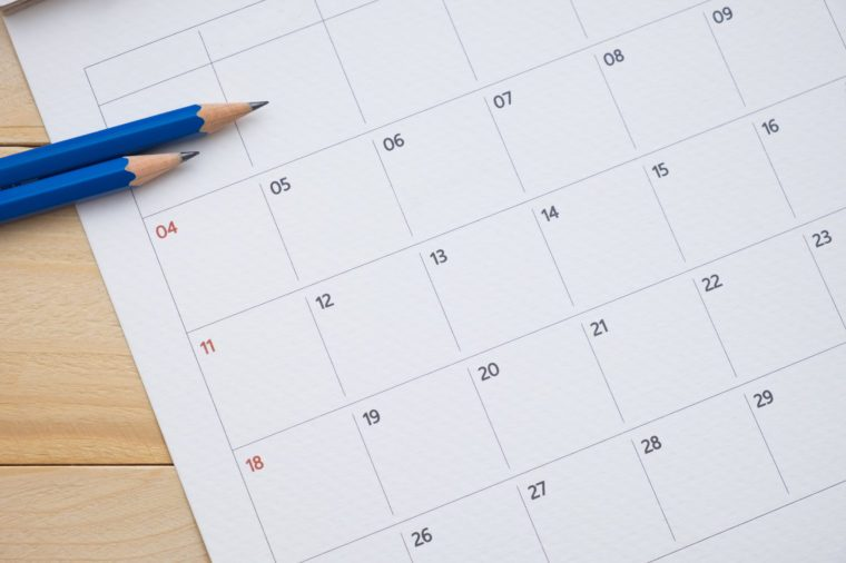 close up calender date and pencil on wooden background