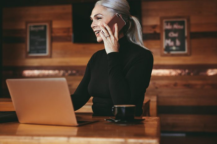 Beautiful senior businesswoman sitting at cafe having telephonic conversation with client. Mature female business professional talking on mobile phone while sitting at coffee shop.