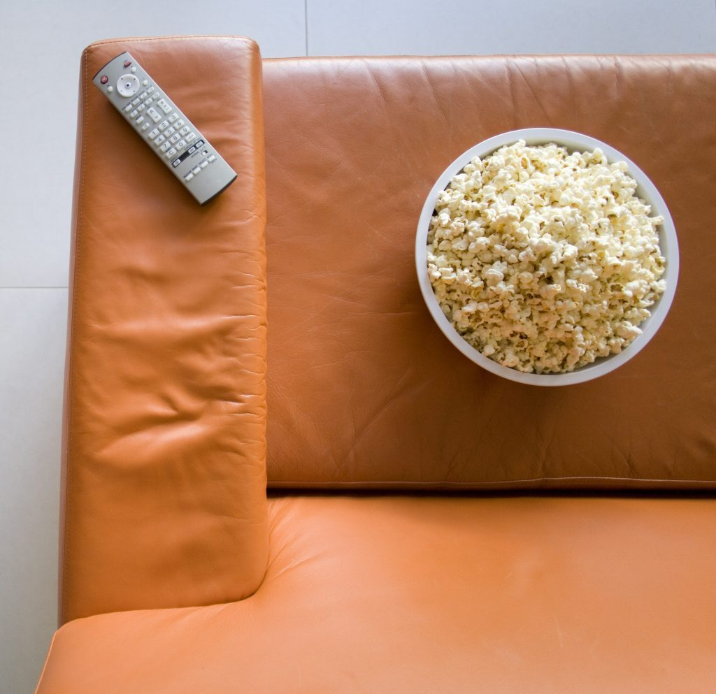 Remote control and bowl of popcorn on orange sofa, elevated view