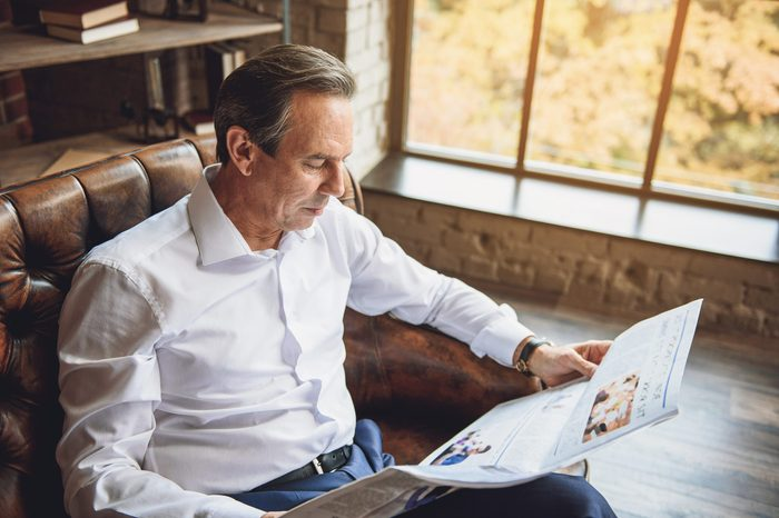 Interested man holding open newspaper