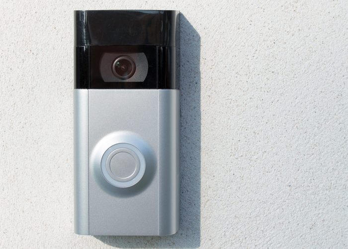 Ring Intercom outdoors on white plastered wall with call and camera, copy space. Close up