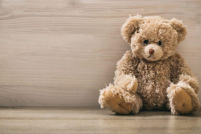 Teddy bear sitting on a wooden background