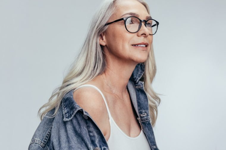 Beautiful senior woman in casuals looking at copy space against grey background. Stylish mid adult caucasian woman in denim shirt and eyeglasses looking away.