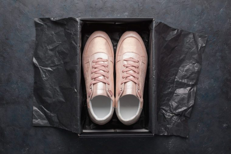 Pair of pink sneakers in shoe cardboard box on black background. Active running (walking) footwear.