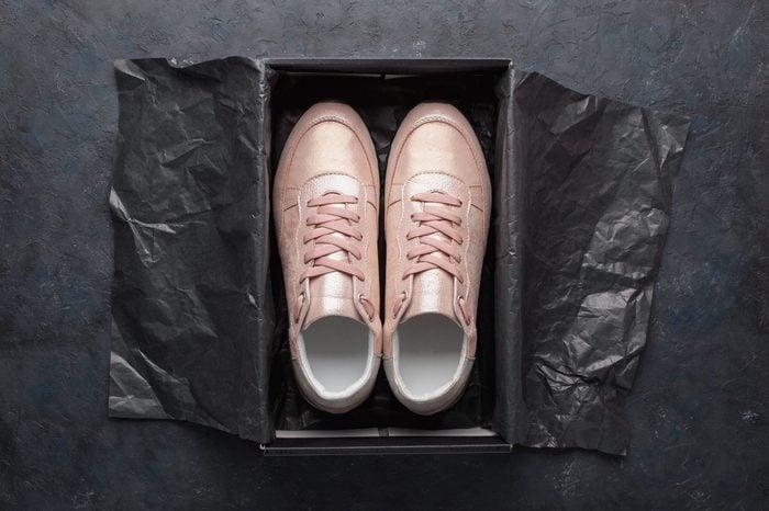 Pair of pink sneakers in shoe cardboard box on black background. Active running (walking) footwear.