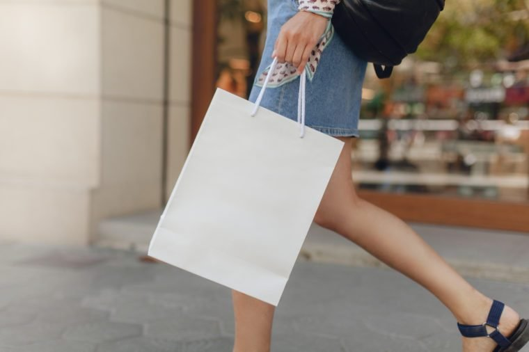 Mockup of white paper shopping bag. Attractive girl doing shopping in shopping mall. Space for your logo or design. Blurred shop window on the background