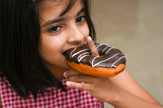 Young Indian girl child eating her chocolate doughnut or donut Mumbai, India.