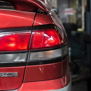 Bangkok, Thailand 14 May 2018 : Tail lights of red car that being repaired in a garage
