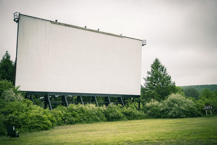The Mahoning Drive-In Theater movie screen stands in the distance; surrounded by grass and wooded overgrowth