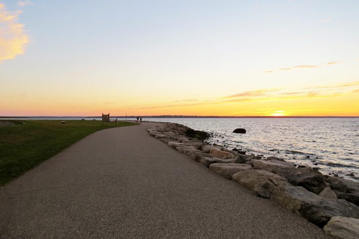 A tranquil path along a rocky seashore at sunset; Colt State Park, Rhode Island