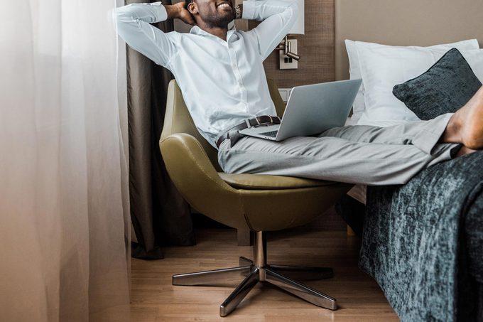 man hotel room relax laptop