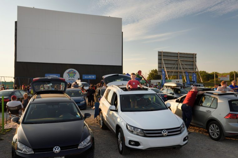 Standing boy looking out sunroof at Volkswagen drive in movie theatre event in Oakville Canada at sundown