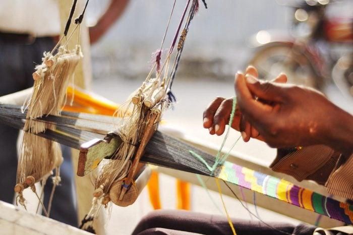 Hands weaving kente cloth - antient craft of Ghana