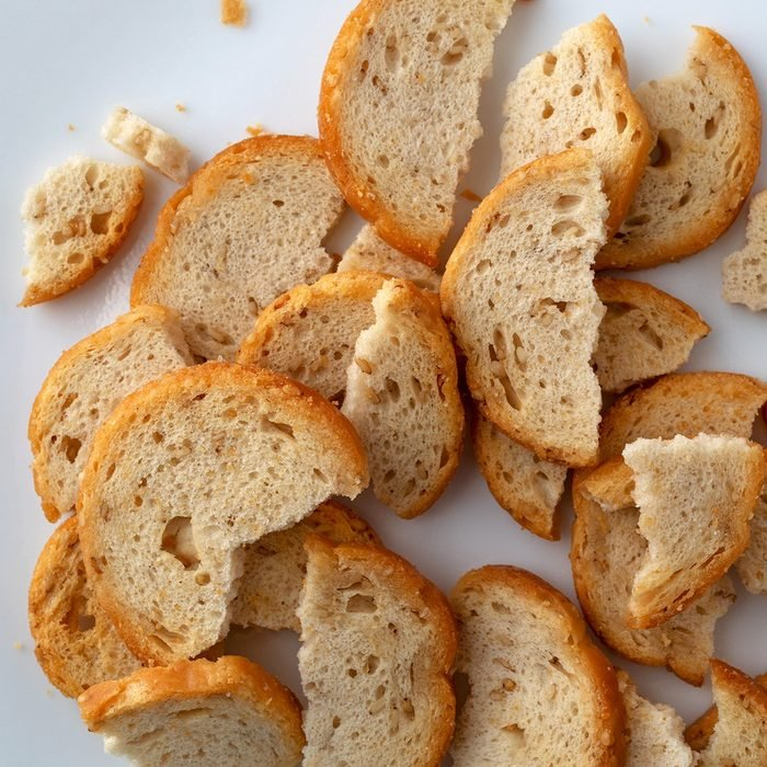 Overhead close view of broken pieces of sesame round melba toast on a white plate.; Shutterstock ID 1284342067; Job (TFH, TOH, RD, BNB, CWM, CM): TOH