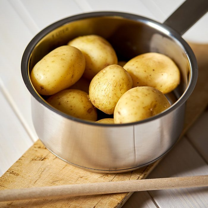 Young potatoes boiled in pot on wooden board on white wooden table; Shutterstock ID 1398365882; Job (TFH, TOH, RD, BNB, CWM, CM): TOH