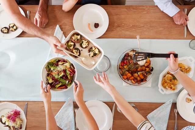 Three generation white family sitting at a dinner table together serving a meal, overhead view