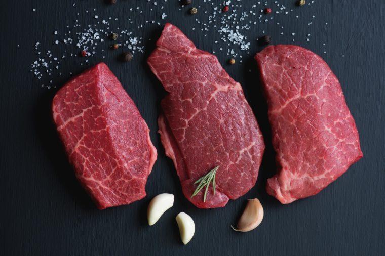 Top view of black angus beef steaks with seasonings, studio shot