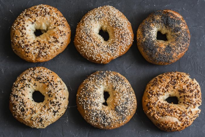 Homemade bagels with a variety of seeds on a gray background, top view. Food background.