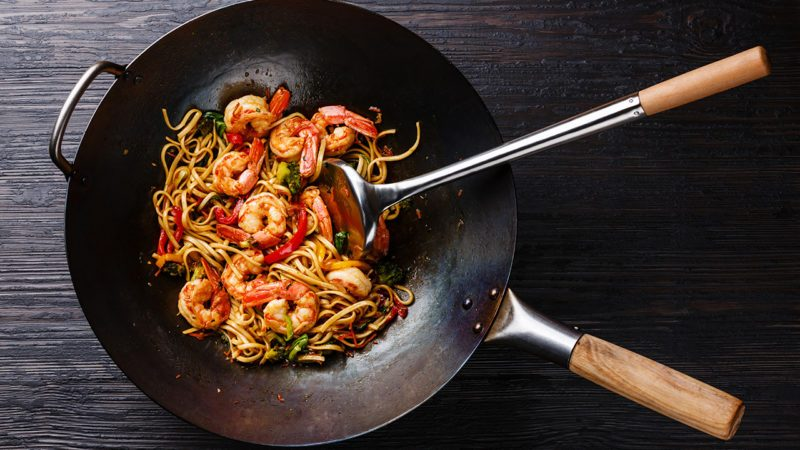 Udon stir-fry noodles with shrimp and vegetables in wok pan on black burned wooden background
