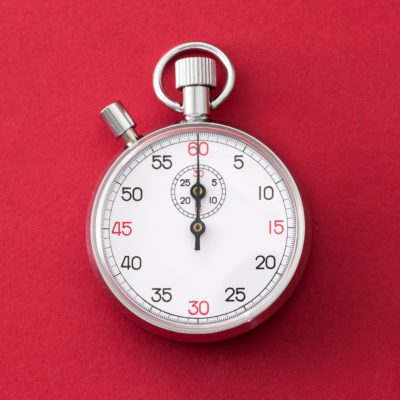 Analogue metal stopwatch on the red background.