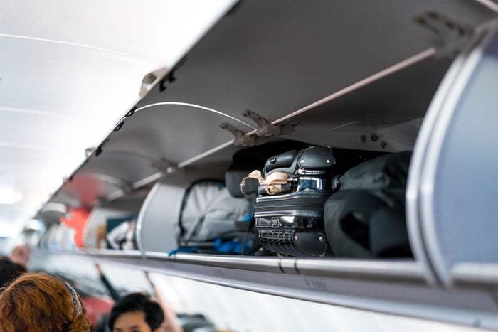 luggage on airplane shelf overhead passenger seat