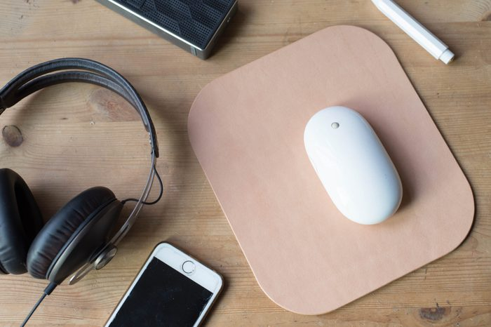 Wood work surface with a mobile phone, headphone, wireless speaker, pencil, mouse and a leather mouse pad.