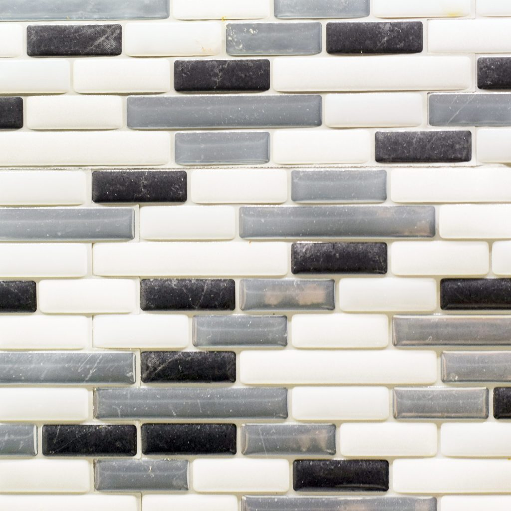 Black white and gray glass tile backsplash in a kitchen