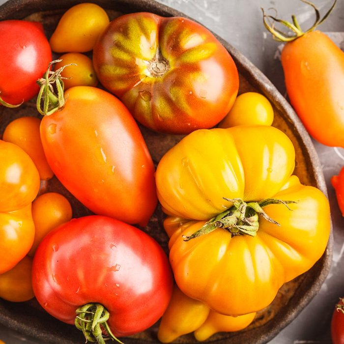 Different types of tomatoes, dark background.