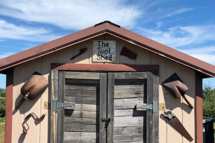 Close view of a tool shed. Old vintage & rusty tools are displayed on the exterior of the building. Beautiful blue skies are visible in the background