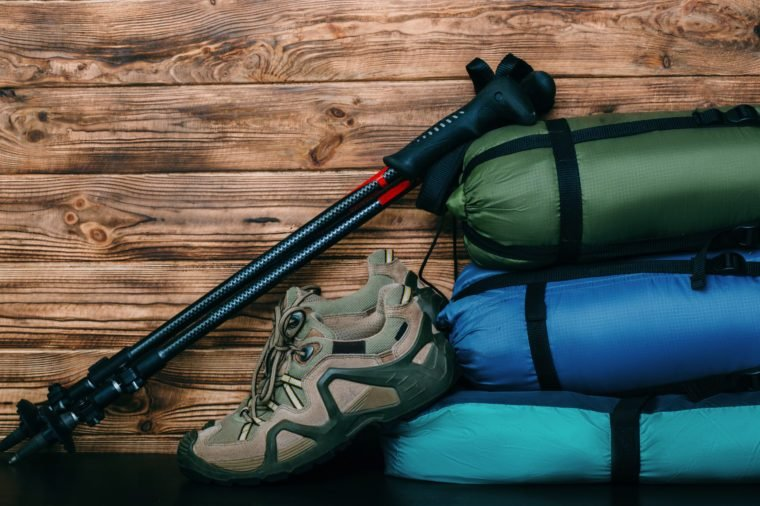 tourist lifestyle with trekking shoes, sleeping bags, tent and trekking poles on wooden background with copy space for text