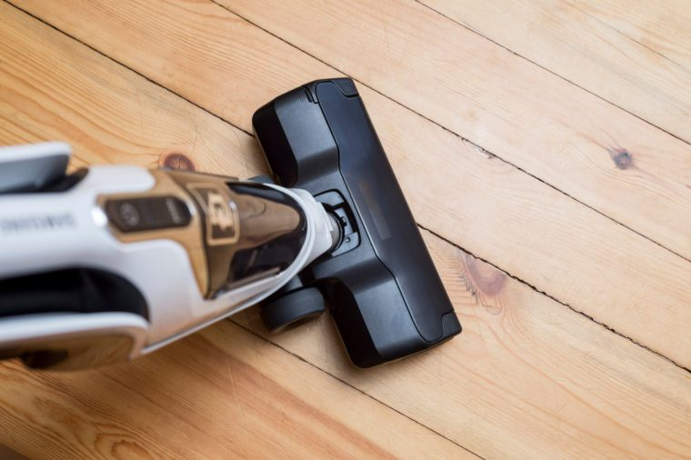 Vacuum cleaner on the wooden floor. Vacuum cleaner on the floor showing house cleaning concept.