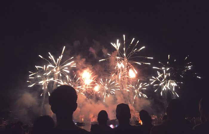 Crowd of Silhouetted People Watching a Fireworks Display for New Years or Fourth of July Celebration, Horizontal