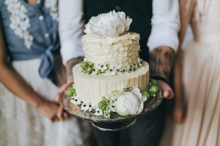 Couple in their wedding clothes holding a white cake decorated with flowers, berries and herbs