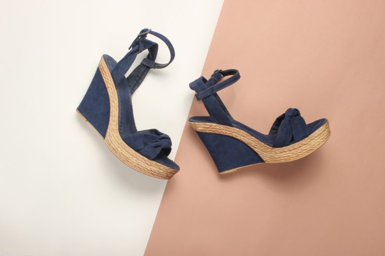 Female sandals on a platform on a colored paper background. on form. Fashionable summer shoes