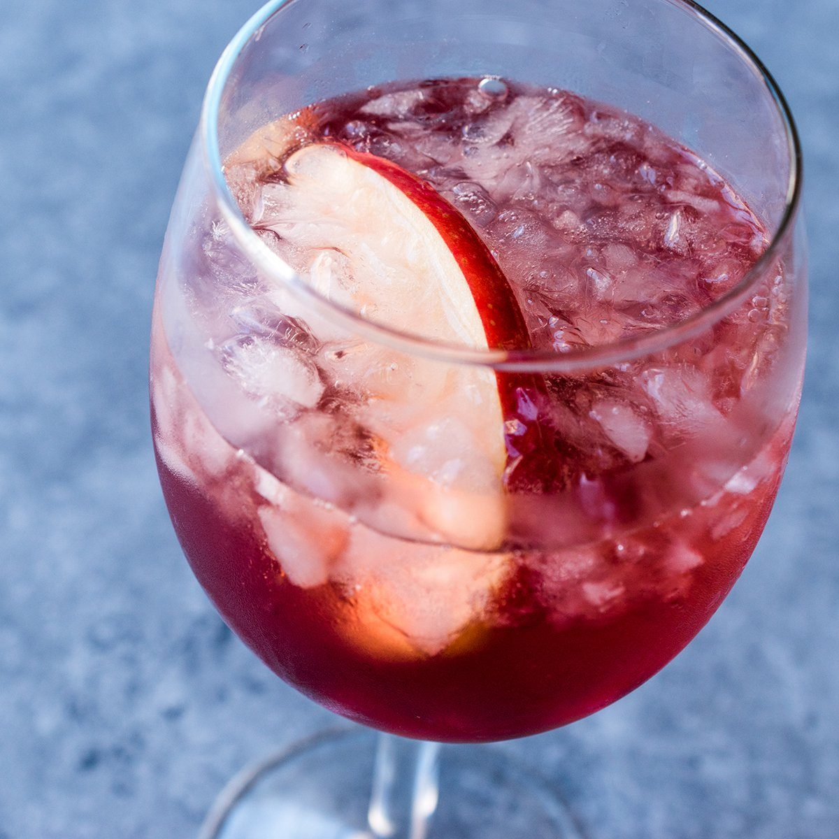 Rose Pink Blush Wine Cocktail with Pomegranate Seeds, Apple Slice and Crushed Ice.