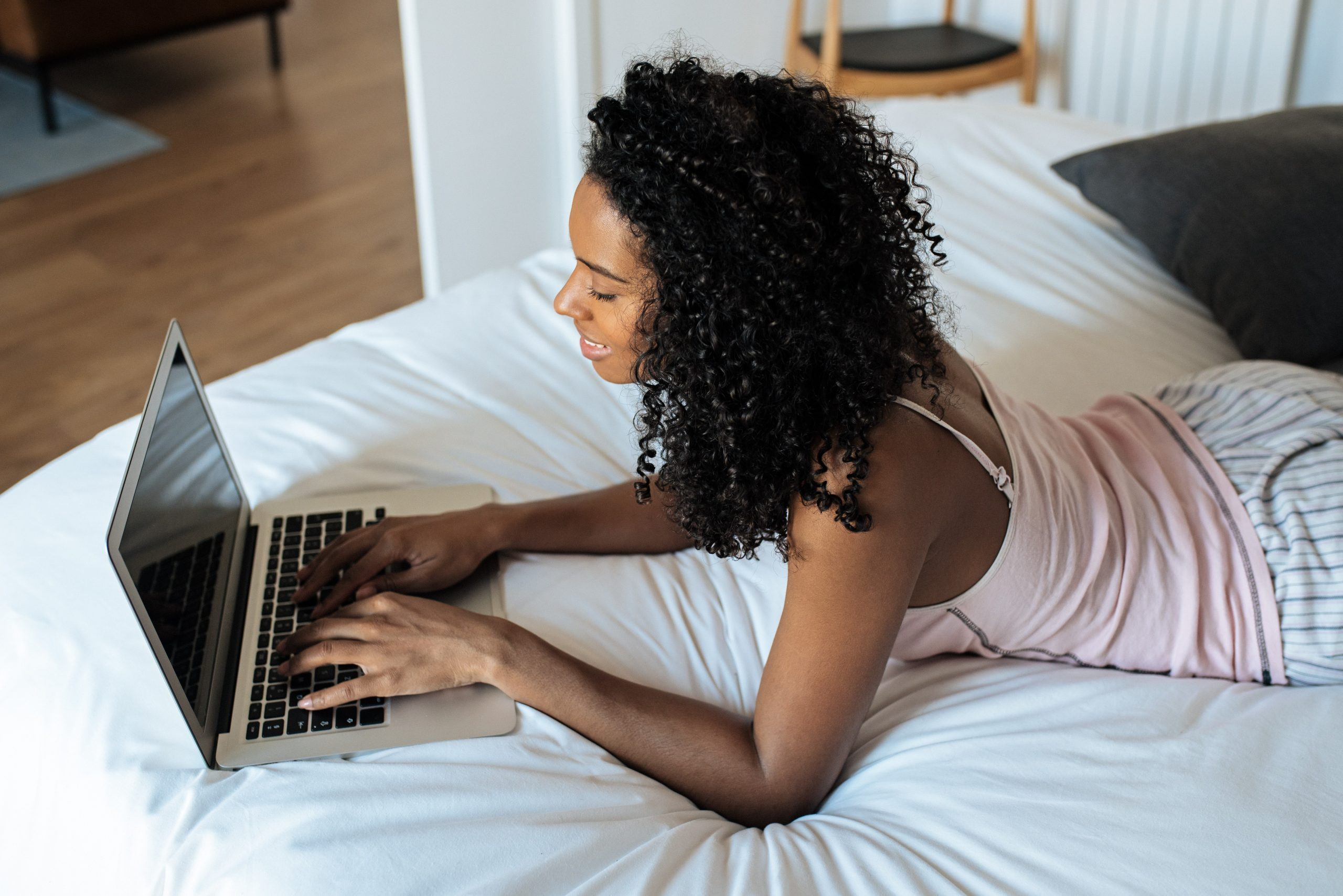 Attractive black woman sitting on bed at home working on the computer