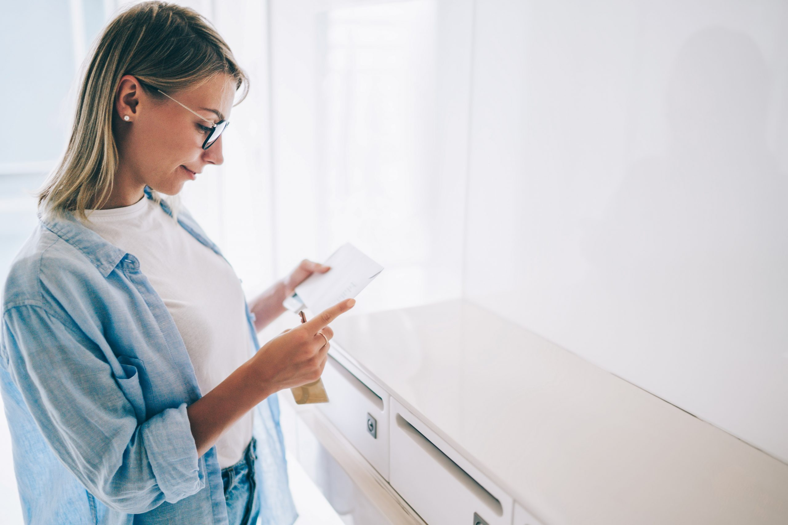Positive caucasian young woman holding received envelope checking mail from metal letterbox in apartment,pretty caucasian hipster girl in spectacles reading correspondence from postal delivery