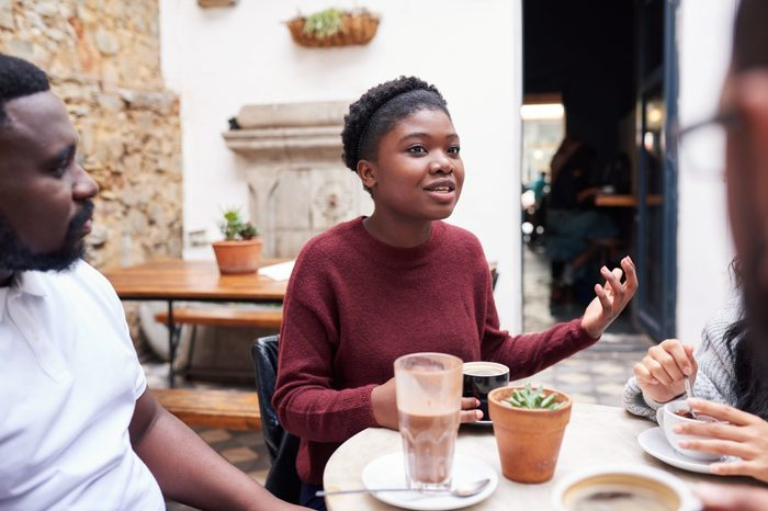 Young African woman talking with friends over coffee while sitting together around a table in the courtyard of a trendy cafe
