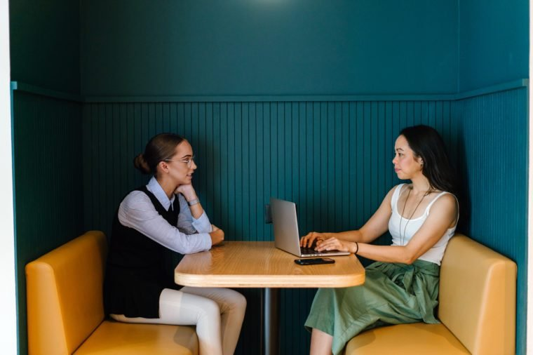 A Caucasian and Asian woman sit in a trendy booth in an office and have a business discussion in the office. They are both young, attractive and are having a focused talk about work.