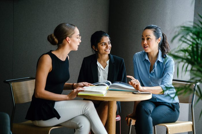A young Indian Asian woman is having a casual business meeting with her team in a meeting room. They are sitting and having an animated conversation. The team is diverse (Caucasian and Chinese woman).