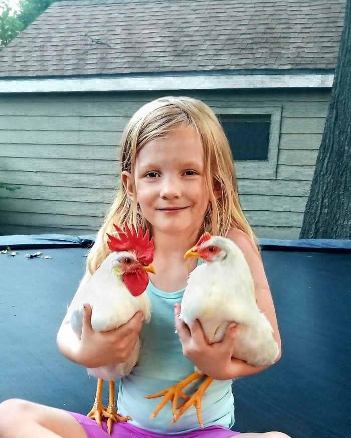 young girl holding a chicken in each arm