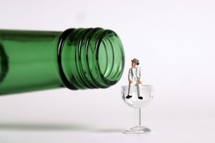 A bottle and a glass. Miniature man sitting on the miniature glass.