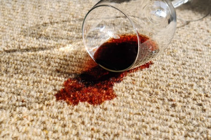 A glass of red wine, spilt on a pure wool carpet.