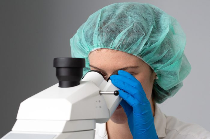 A pretty girl scientist is seen up close, looking through a professional microscope inside a biochemistry laboratory, with room for copy.